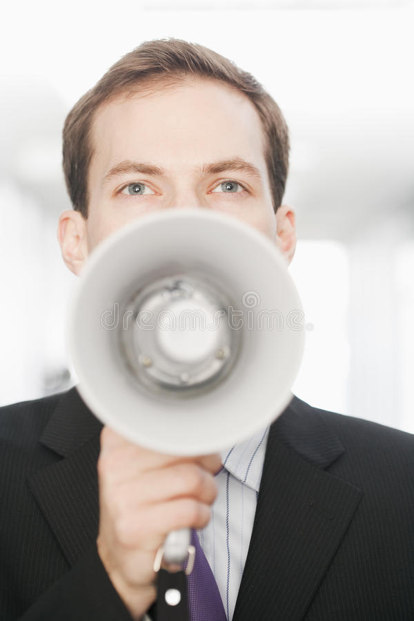 Handsome Young Businessman With Bullhorn. Handsome young businessman speaks through a bullhorn. Vertical shot royalty free stock images