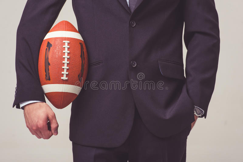 Handsome young businessman. Cropped image of handsome young businessman in suit holding a football ball, on a gray background royalty free stock photos