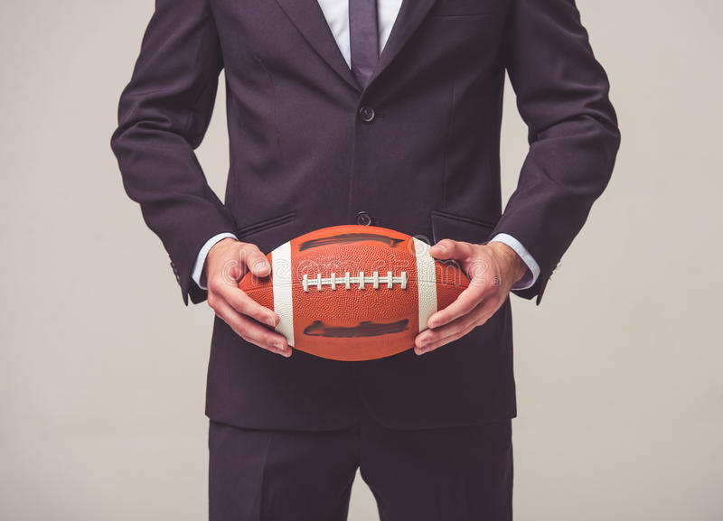Handsome young businessman. Cropped image of handsome young businessman in suit holding a football ball, on a gray background stock photography