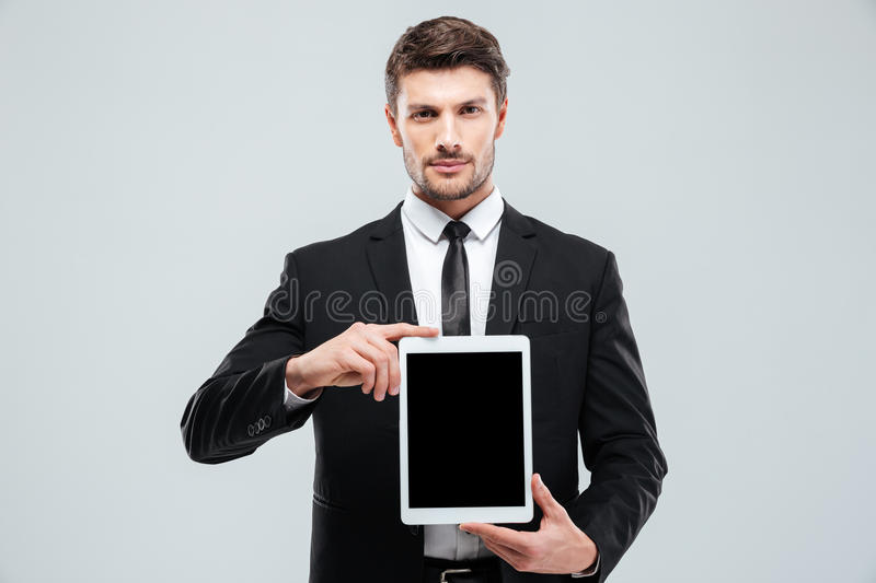 Handsome young businessman holding blank screen tablet. Over white background royalty free stock photos