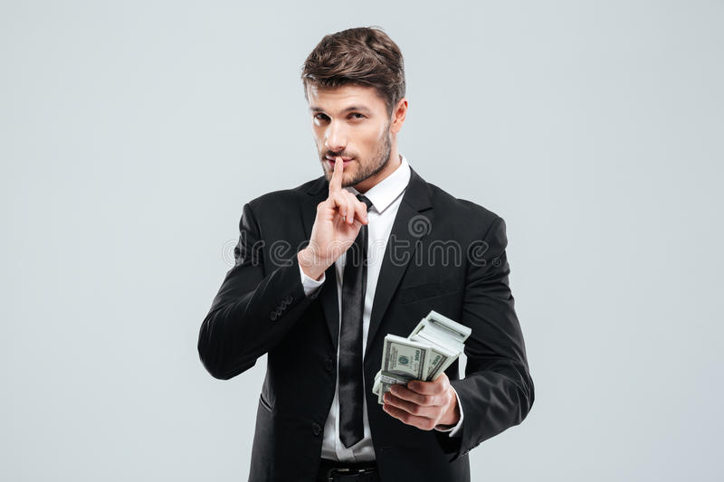 Handsome young businessman holding money and showing silence sign. Over white background royalty free stock photo