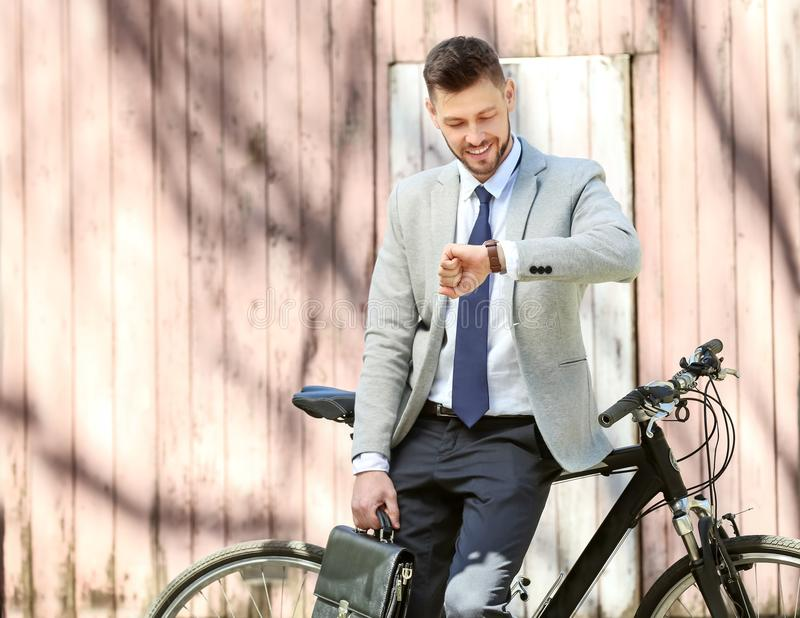 Handsome young businessman looking at watch while standing near bicycle outdoors. On sunny day royalty free stock photos