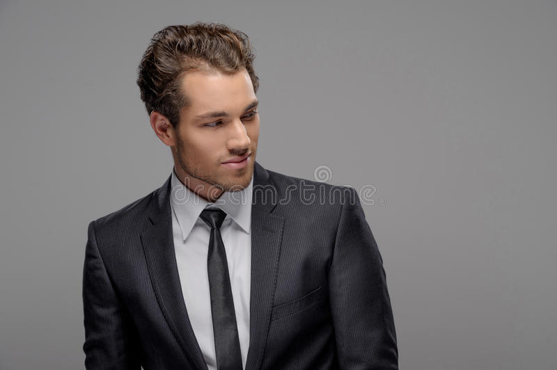 Handsome young businessman. Portrait of handsome young businessmen looking away while standing isolated on grey royalty free stock photo