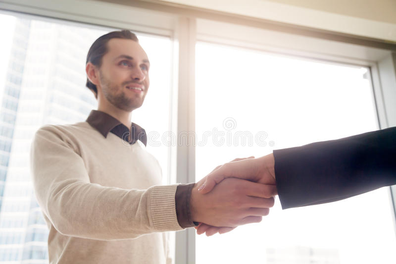 Handsome young businessman shaking female hand, deal or business stock photo