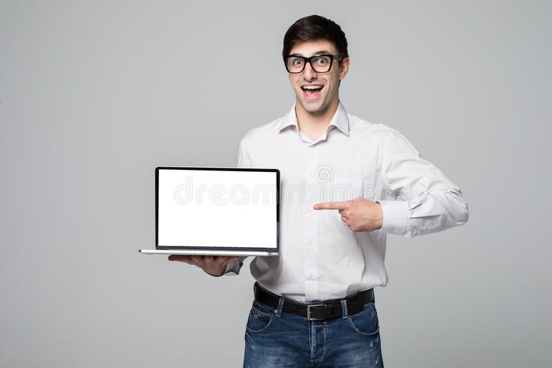 Handsome young businessman showing blank screen laptop over gray background royalty free stock image