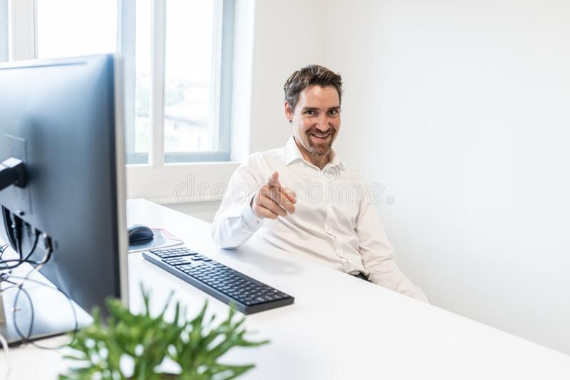 Handsome young businessman pointing with his finger towards you stock images