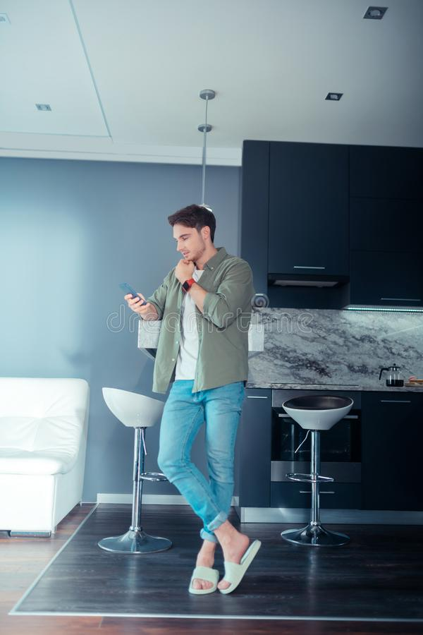 Handsome young businessman standing in spacious kitchen royalty free stock photography