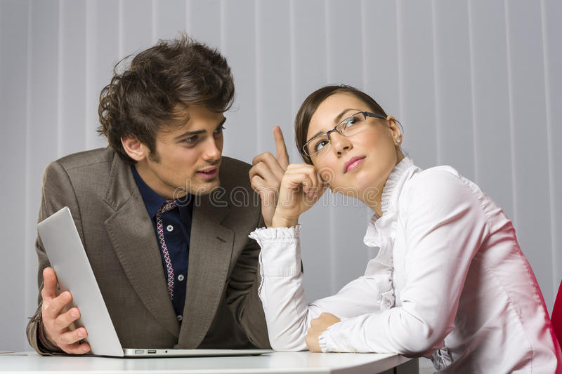 Business team issue. Handsome young businessman trying to convince his abstracted, pensive, looking away business women partner at work stock photos