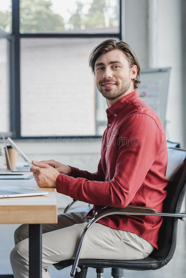 handsome young businessman using digital tablet and smiling at camera royalty free stock photos
