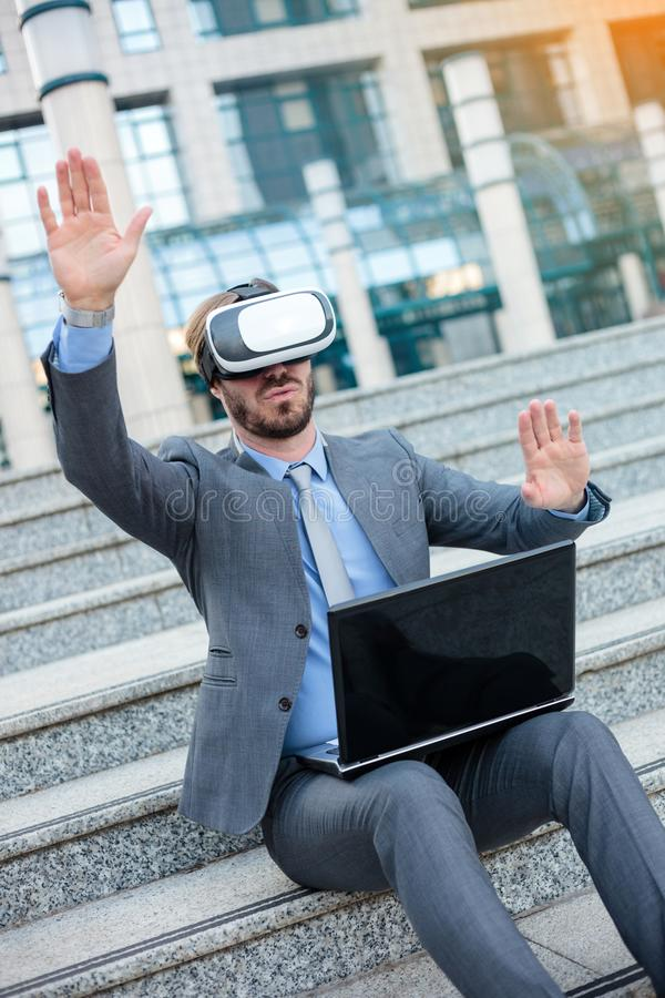 Young businessman using VR goggles and making hand gestures, working on a laptop in front of an office building royalty free stock photo