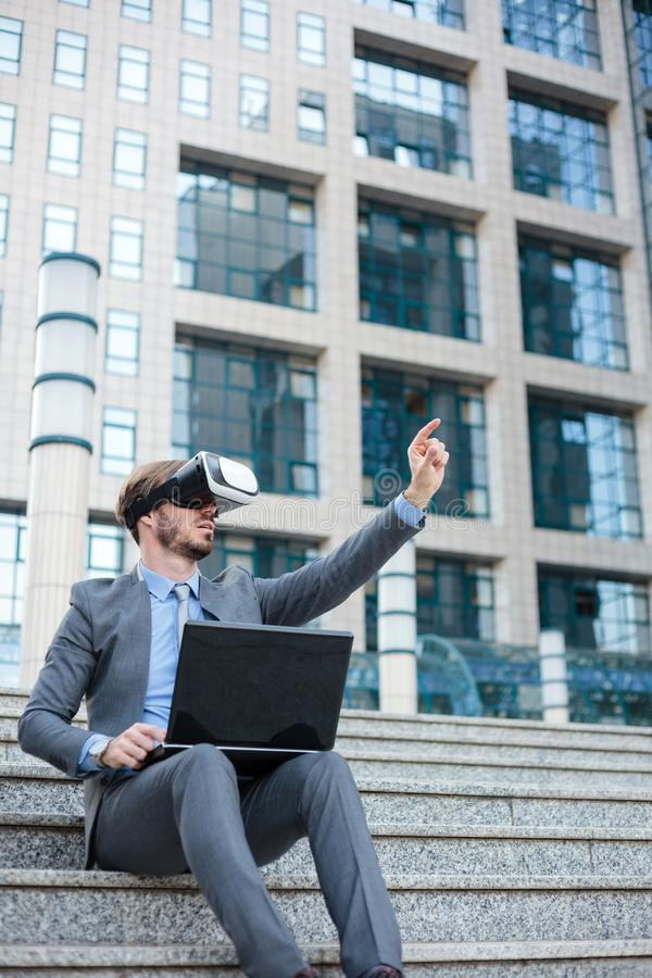 Handsome young businessman using virtual reality simulator and making hand gestures, working on a laptop in front of an office bui stock photography