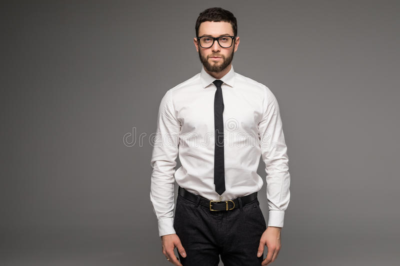 Handsome young businessman in white shirt and tie standing and glasses over grey background royalty free stock photos
