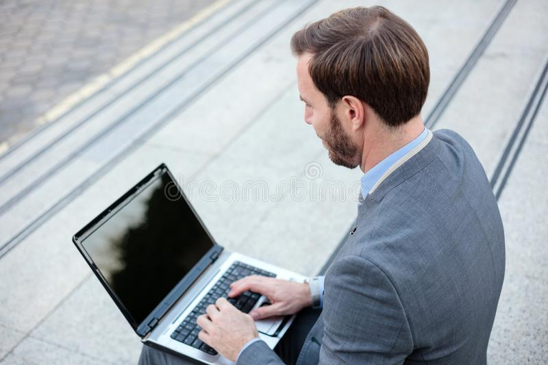 Handsome young businessman working on a laptop in front of an office building. High angle view stock images