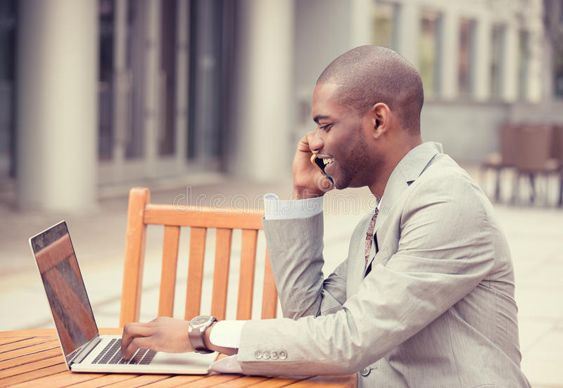 Handsome young businessman working with laptop outdoors talking on mobile phone royalty free stock photography