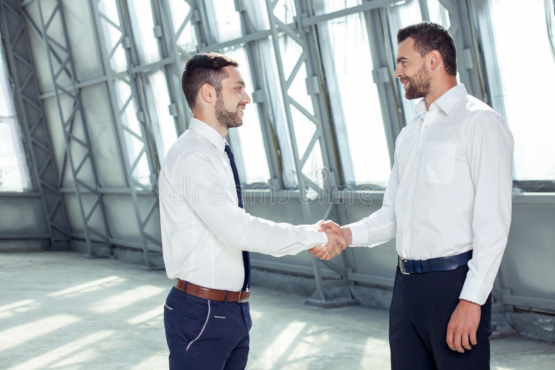 Handsome young businessmen are greeting each other. Attractive business partners are shaking hands and smiling. They made a deal. The men are standing and stock photos