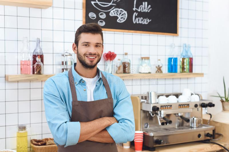 handsome young cafe owner in apron standing with crossed arms and smiling stock photos