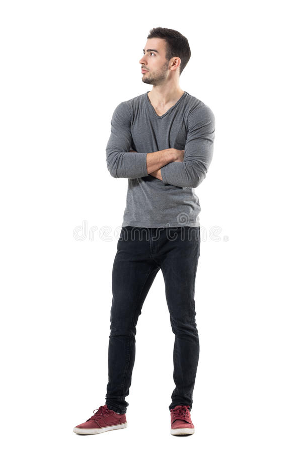 Handsome young casual man with crossed hands looking away stock image