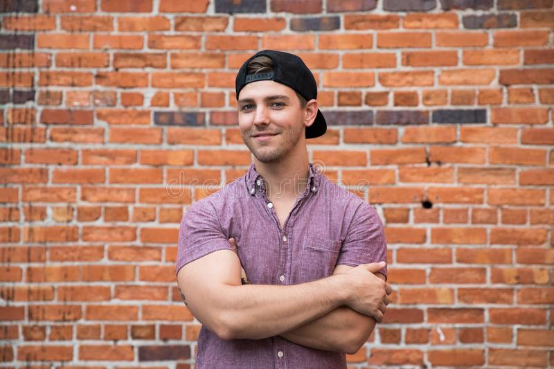 Handsome Young Caucasian Man with Cellphone and Backwards Hat Smiling for Portraits in Front of Textured Brick Wall Outside stock photography