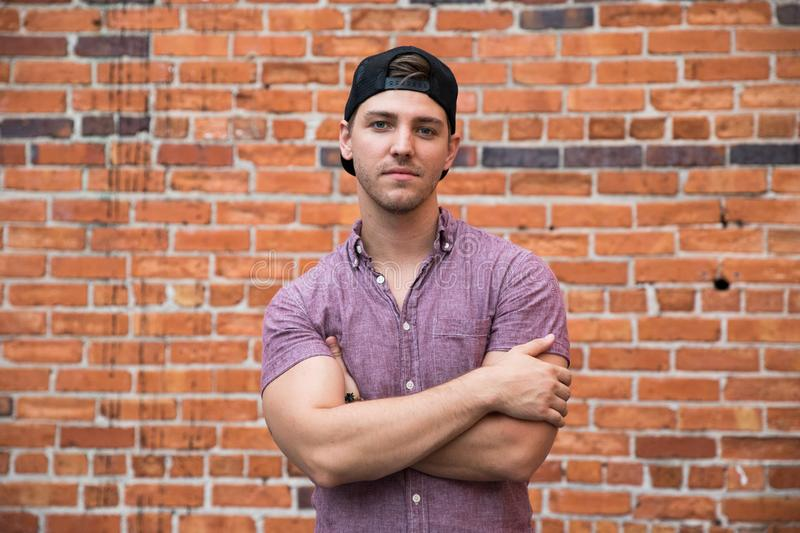 Handsome Young Caucasian Man with Cellphone and Backwards Hat Smiling for Portraits in Front of Textured Brick Wall Outside stock image