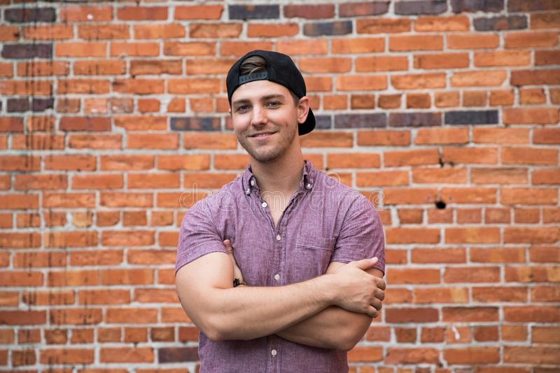 Handsome Young Caucasian Man with Cellphone and Backwards Hat Smiling for Portraits in Front of Textured Brick Wall Outside royalty free stock images
