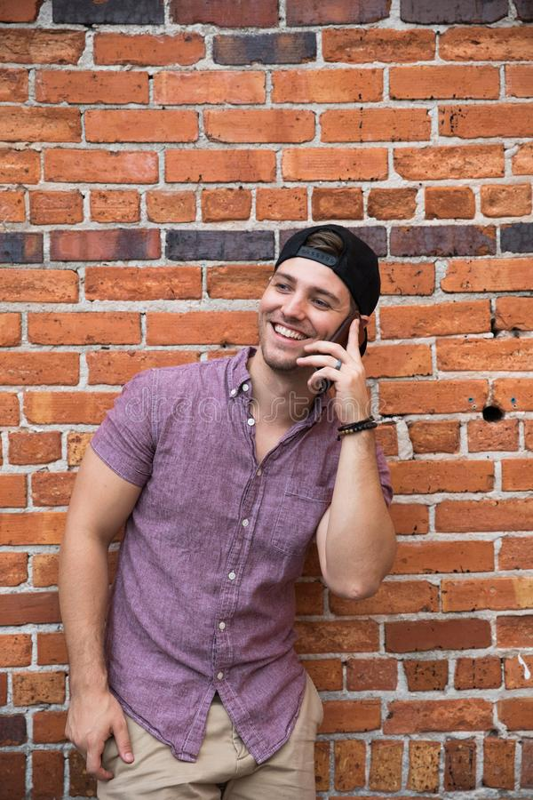 Handsome Young Caucasian Man with Cellphone and Backwards Hat Smiling for Portraits in Front of Textured Brick Wall Outside royalty free stock photo