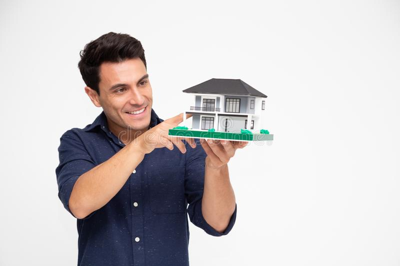 Handsome young Caucasian man inspector holding single home, Home inspection service before transferring to house royalty free stock photography