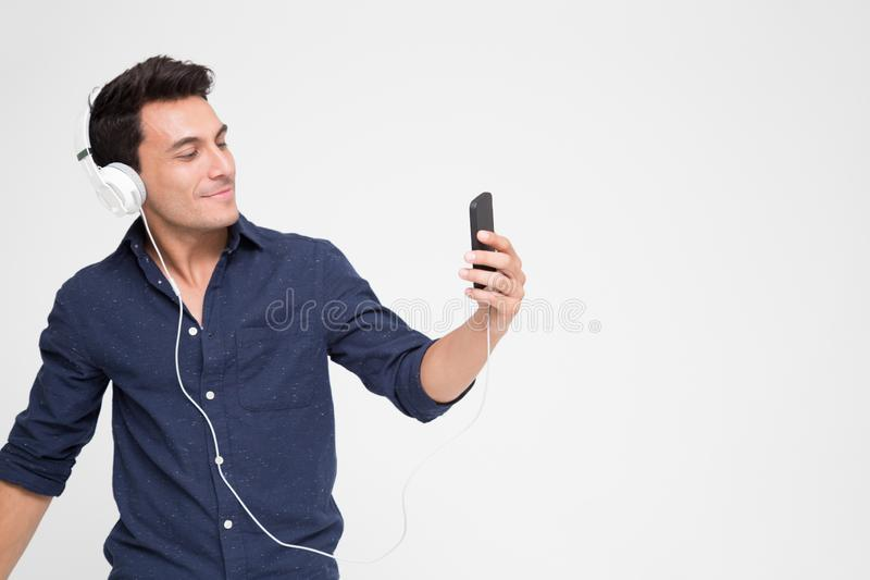 Handsome young Caucasian man listening music with headphones on smartphone, royalty free stock photography