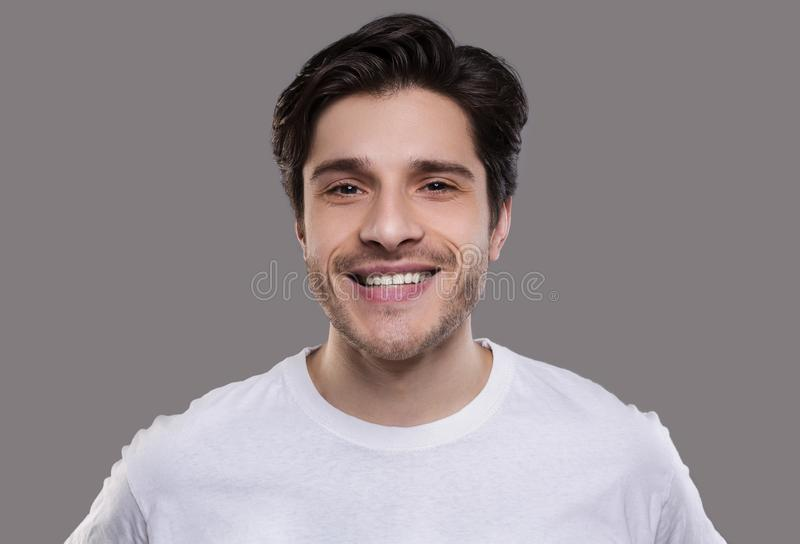 Handsome young caucasian man smiling at camera stock image