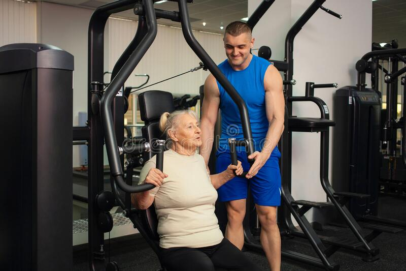 A Handsome Young Coach Man Helps An Old Woman Train Sports