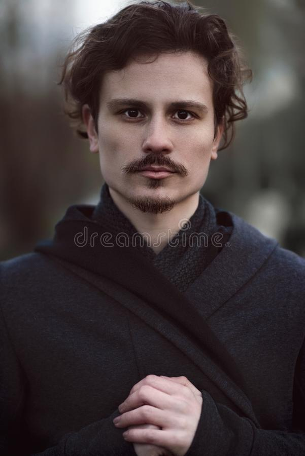Handsome young curly man sincerely prays to God royalty free stock images