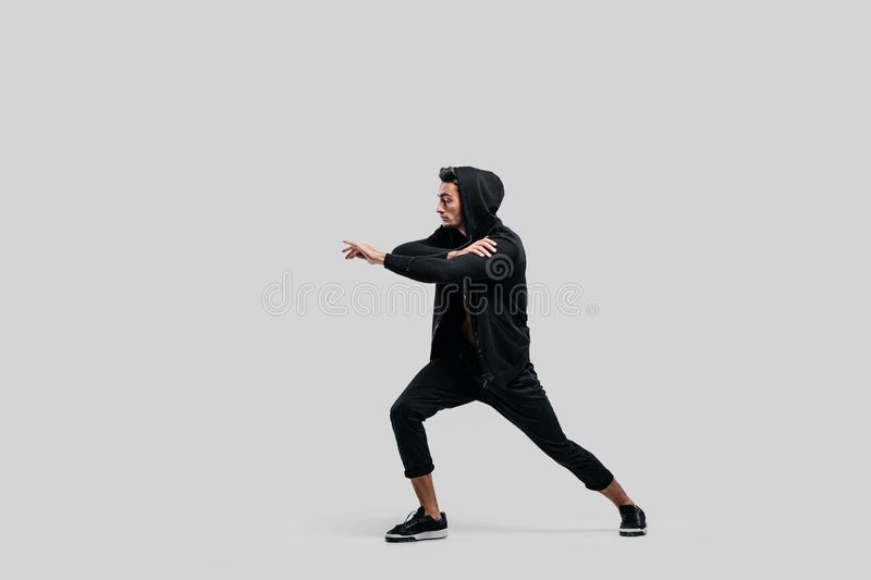 Handsome young dancer of street dancing dressed in black pants, a sweatshirt on a naked torso and a hood dances on a royalty free stock photos