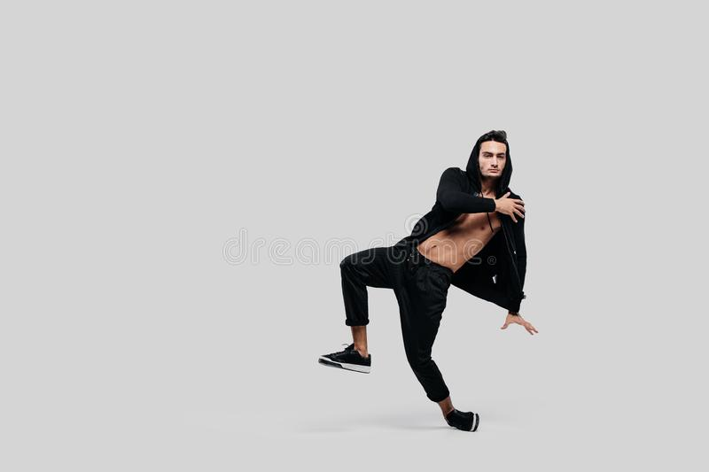 Handsome young dancer of street dancing dressed in black pants, a sweatshirt on a naked torso and a hood dances on a stock photo