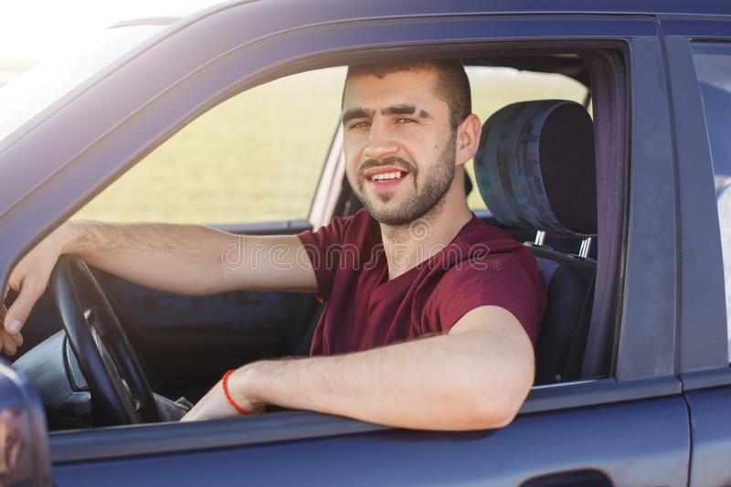 Handsome young dark haired male with stubble dressesd maroon casual t shirt, poses in black car, looks at camera trough window, royalty free stock image