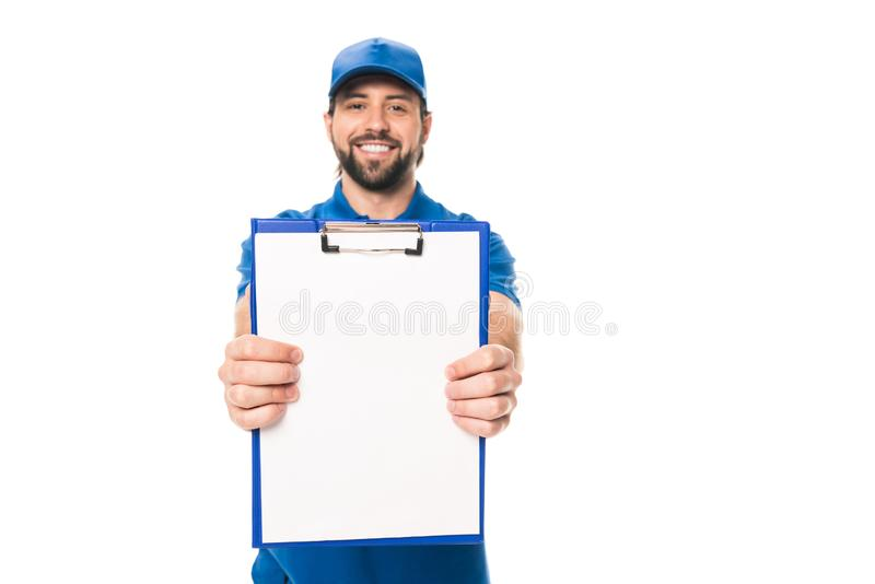 handsome young delivery man holding blank clipboard and smiling at camera royalty free stock photo