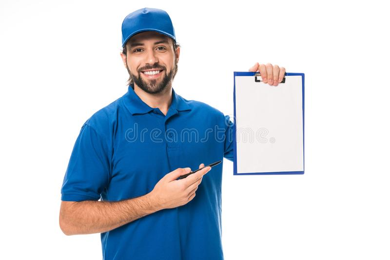handsome young delivery man pointing at blank clipboard and smiling at camera stock image