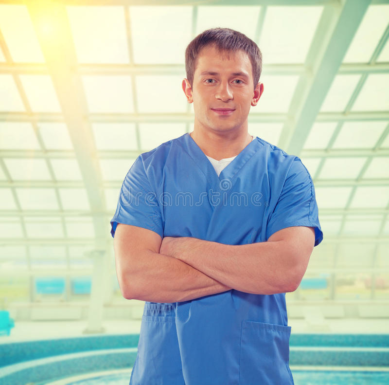 Handsome young doctor with crossed arms looking at camera on background of big window instagram stile stock photo