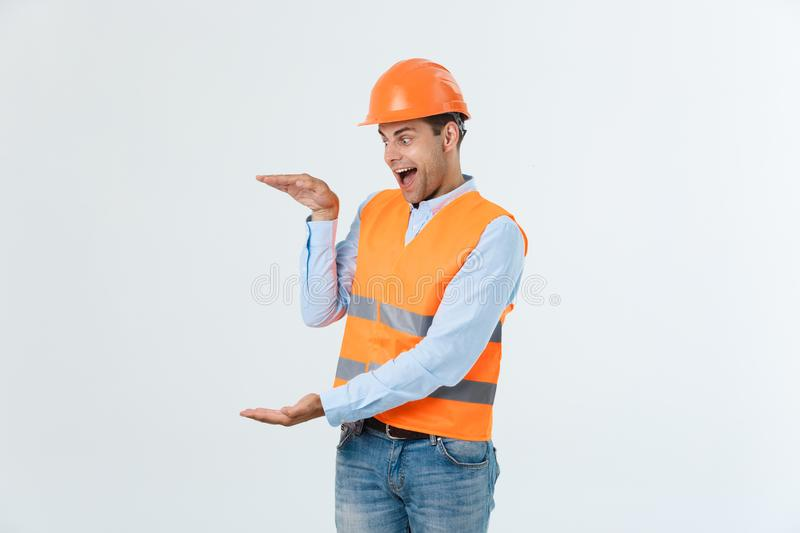 Handsome young engineer man over grey wearing safety helmet with shocked surprise face. stock image
