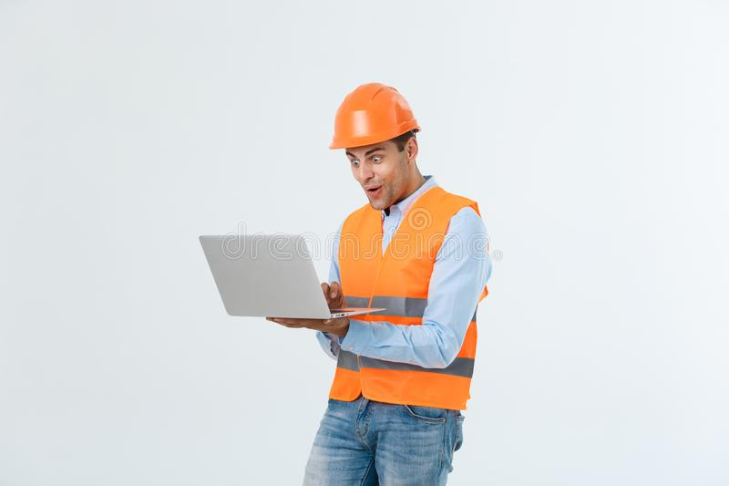 Handsome young engineer man over grey wearing safety helmet with shocked surprise face. royalty free stock photos