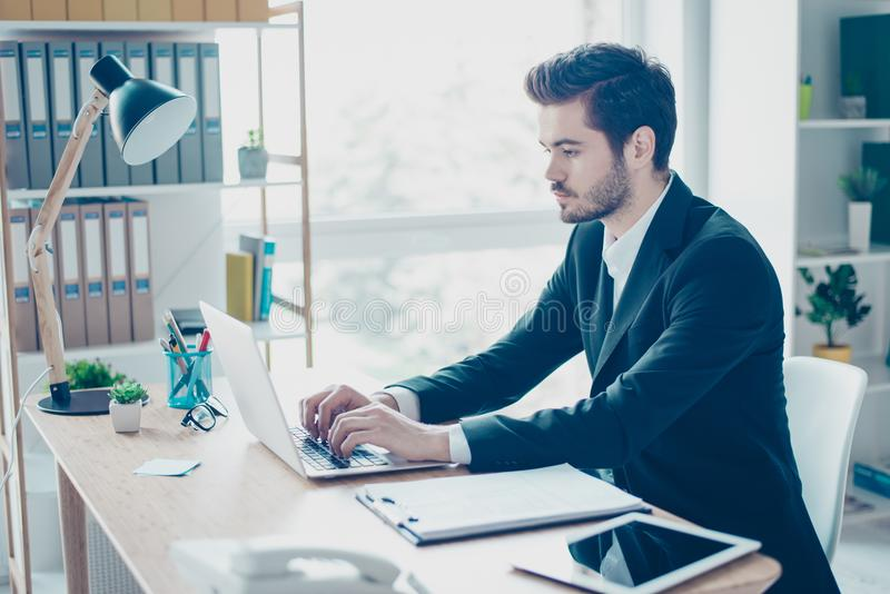 Handsome young entrepreneur in formal-wear sitting at the table. At his office and searching information in the internet stock photo