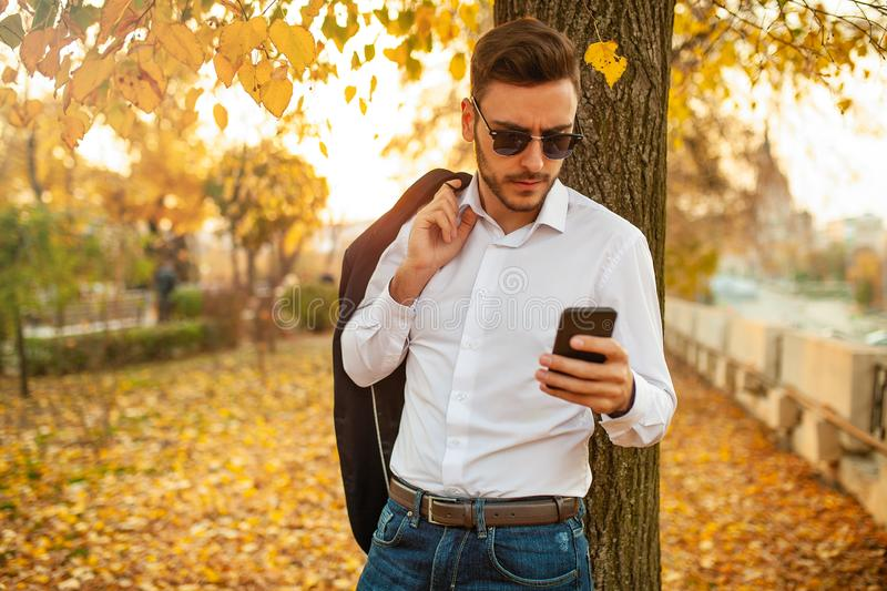 Handsome young fashionable man in a stylish business suit and sunglasses is typing a message royalty free stock photo