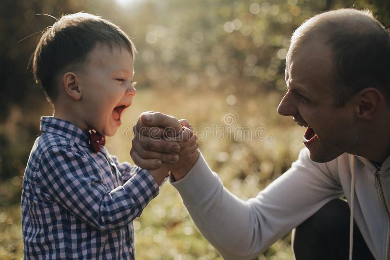 Handsome young father son competing in arm wrestling with cheerfull young son with bow tie. Autumn forest stock photos