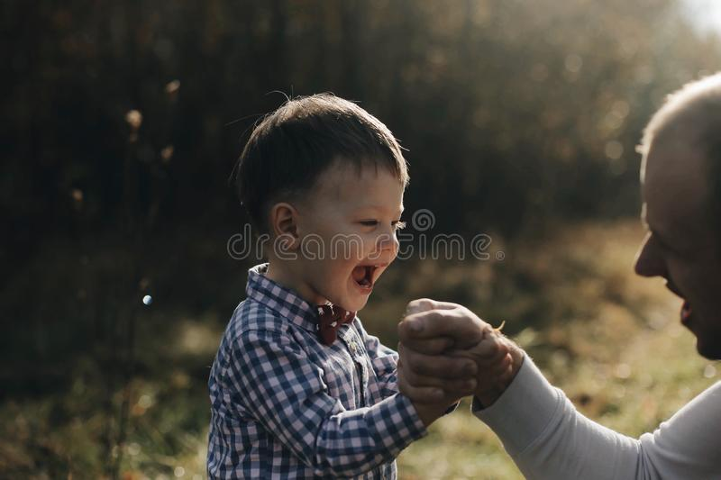 Handsome young father son competing in arm wrestling with cheerfull young son with bow tie. Autumn forest royalty free stock photo