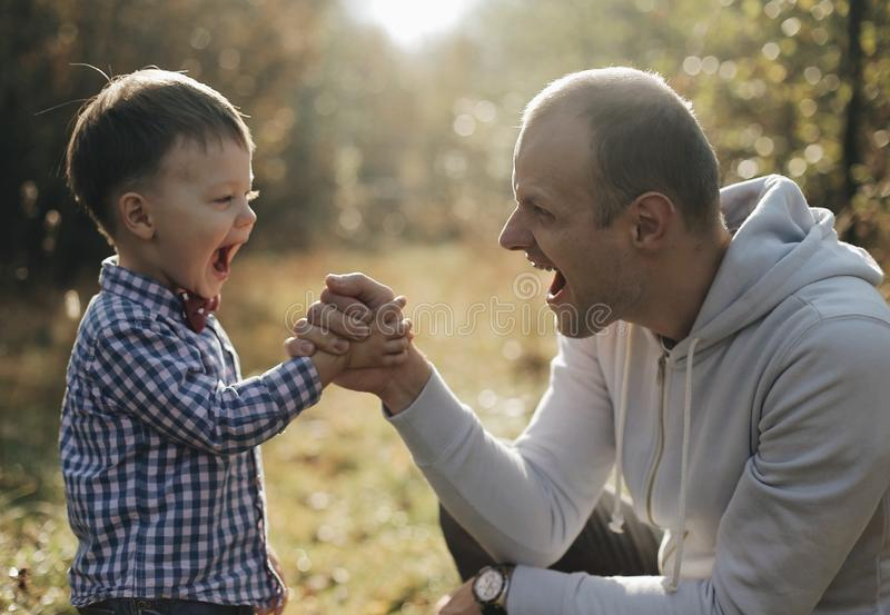 Handsome young father son competing in arm wrestling with cheerfull young son with bow tie. Autumn forest stock image