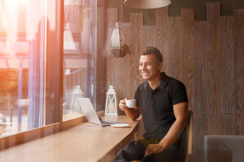 Handsome young freelancer is having a coffee break royalty free stock image