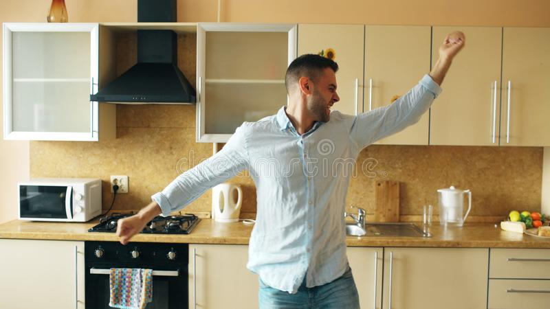 Handsome young funny man dancing in kitchen at home in the morning and have fun on holidays stock photography