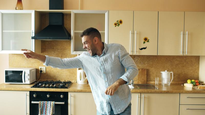 Handsome young funny man dancing in kitchen at home in the morning and have fun on holidays stock images
