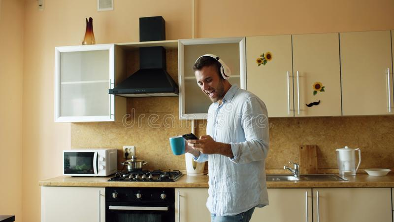 Handsome young funny man in headphones dancing and singing in kitchen at home in the morning and have fun on vacation royalty free stock photos