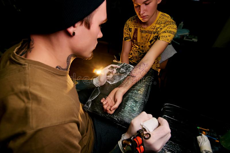 Handsome young guy in a black hat and with tattoos, beats a tattoo on his arm, tattoo salon royalty free stock photography