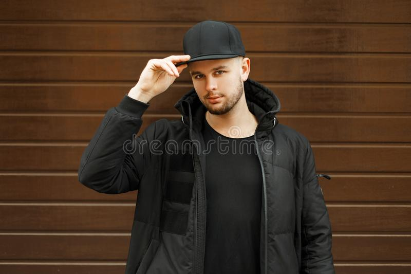 Handsome young guy in a black stylish baseball cap stock photography