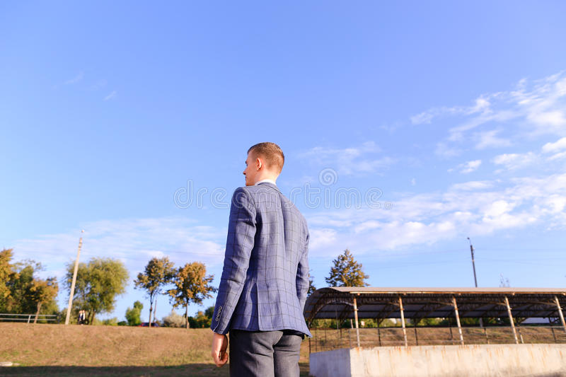Handsome young guy businessman, student stands with his back to stock photography
